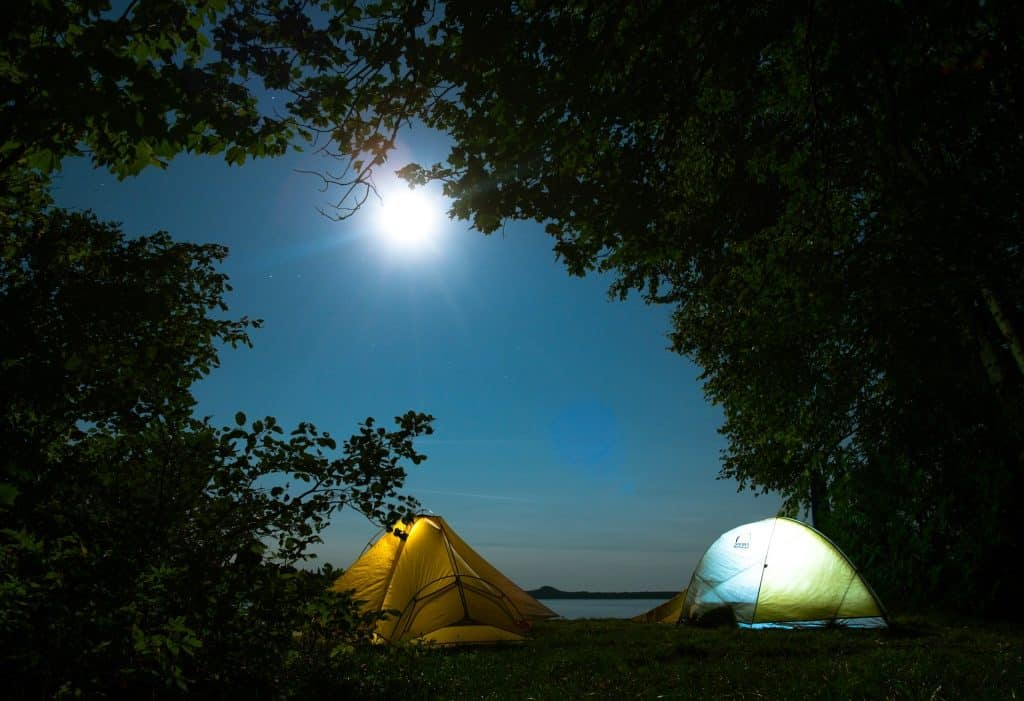 Campsite at night with moon, tents, camping chairs and trekking poles